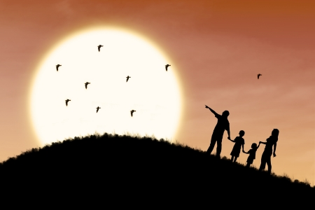Silhouette of a family walking up the hill to enjoy sunset photo