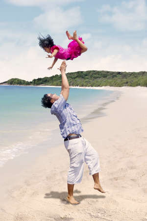 Father and daughter having fun at beach photo