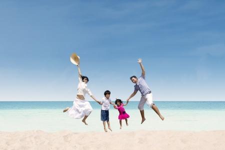 asian family outdoor: Happy family jumping at white sandy beach, Australia Stock Photo