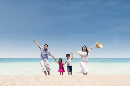Happy Asian family running at beach