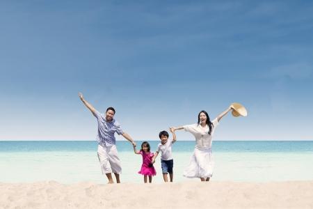 viaje familia: Familia asiática feliz que se ejecuta en la playa