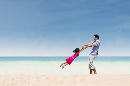 Father lifting her daughter on the beach Stock Photo