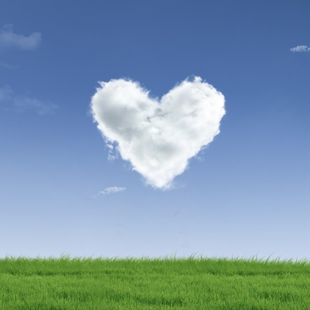 green heart: Picture of a a heart cloud on blue sky  and green field Stock Photo