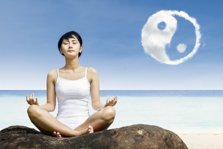 yoga rocks: Woman meditation and ying yang cloud at beach Stock Photo