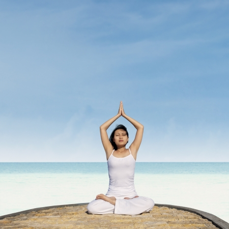Young asian woman practicing yoga at beach. Shot at tropical beach Stock Photo - 19722946