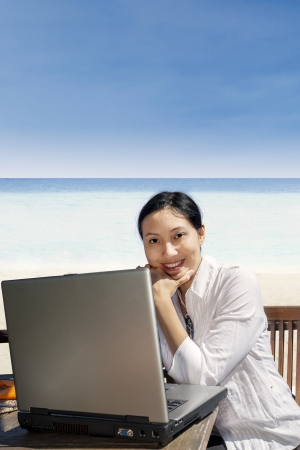 Asian business woman working with a laptop on the beach photo