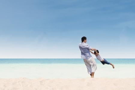 vater und baby: Gl�cklicher Vater und Sohn spielen zusammen am Strand