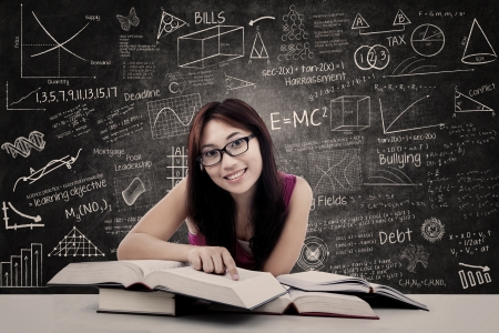 scholar: Happy female student with books and written blackboard