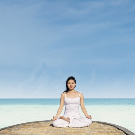 Young woman meditating on the beach. This is the lotus position in yoga. Stock Photo - 19722945
