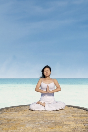 Young asian woman meditating on the beach under blue sky photo