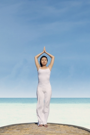 Pretty woman doing yoga on the beach. Shot at tropical beach Stock Photo - 19722944