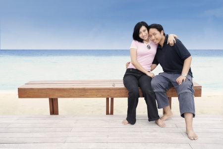 Asian couple hugging at the beach photo