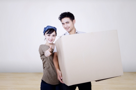 Asian couple bring box to new home photo