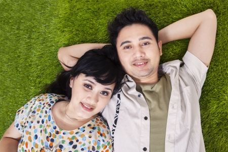 weekend break: Asian couple laying on green grass, shot from above