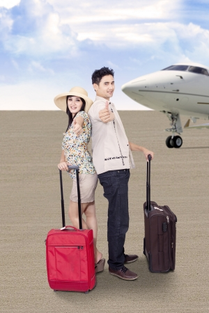 tourist destination: Asian couple is travelling by airplane, carry luggages at the airport