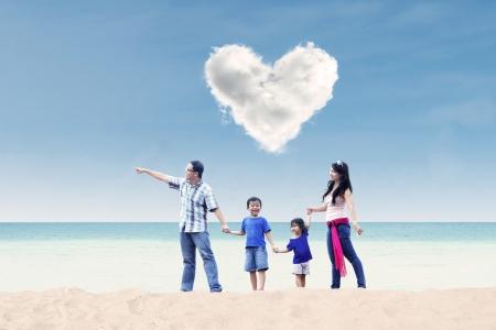 familia viaje: Familia asi�tica disfrutar de tiempo en la playa bajo las nubes del amor Foto de archivo