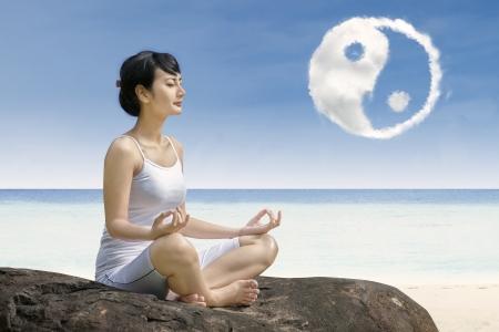 ying yang: Attractive girl at beach exercising yoga , under ying yang cloud