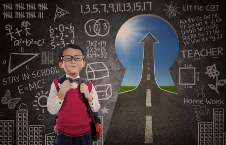 enhancement: Boy student and road to success through a keyhole with written blackboard Stock Photo