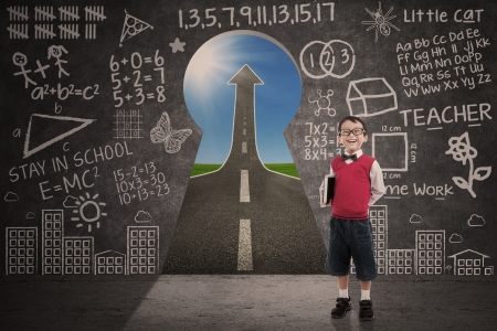 Boy student smiling in class with success road behind keyhole photo
