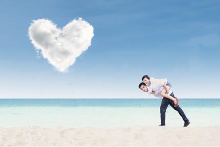 under heart: Boyfriend giving piggyback ride under heart cloud on the beach