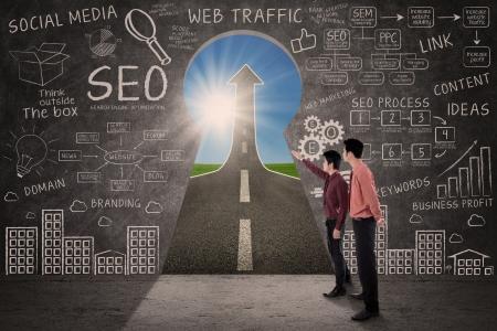 Businessmen talking in front of SEO strategy formulas written on a blackboard photo