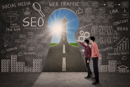 marketing team: Businessmen talking in front of SEO strategy formulas written on a blackboard