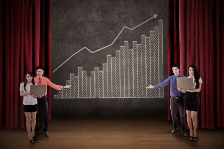 stage chart: Business team present profit bar chart on stage Stock Photo