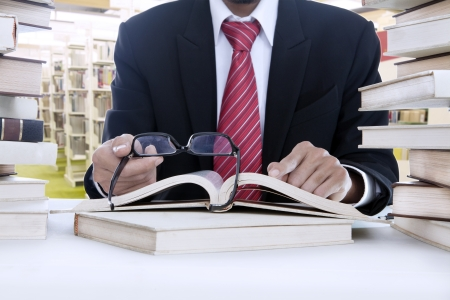 published: Unrecognizable businessman is reading with glasses in the library