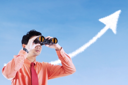 Businessman see success arrow sign using binocular under blue sky photo