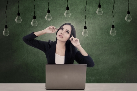 Beautiful businesswoman is thinking of ideas while working with her laptop photo