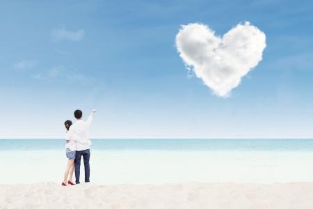 under heart: Couple honeymoon at whitehaven beach under heart cloud