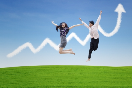 asian couple: Happy couple jumping on profit chart cloud