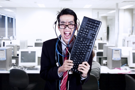 Crazy businessman hold keyboard and cables at office Stock Photo