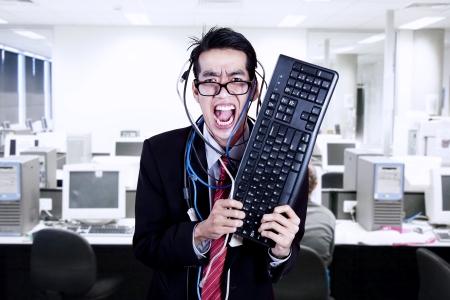 crazy people: Verr�ckter Gesch�ftsmann halten Tastatur und Kabel im B�ro