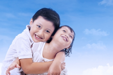 Cute brother and sister hugging under blue sky photo