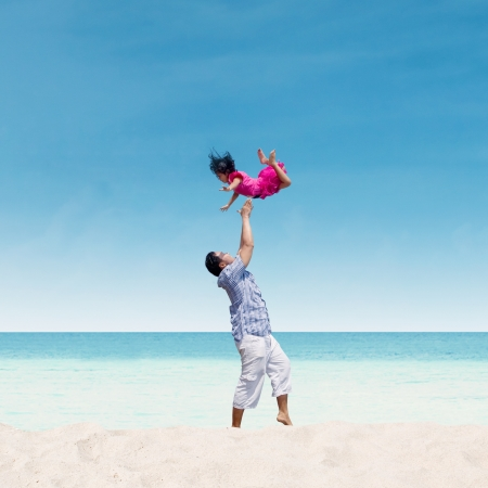 Dad is throwing his daughter up in the air on the beach photo