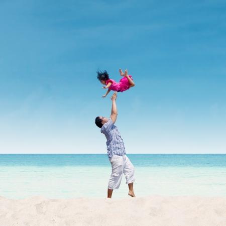 Pap� est� tirando a su hija en el aire en la playa Foto de archivo - 19837116