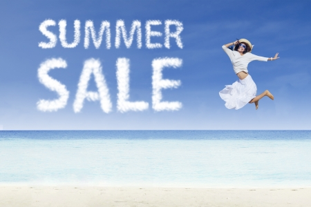 sales person: Girl jumping beside summer sale cloud on white sand Stock Photo