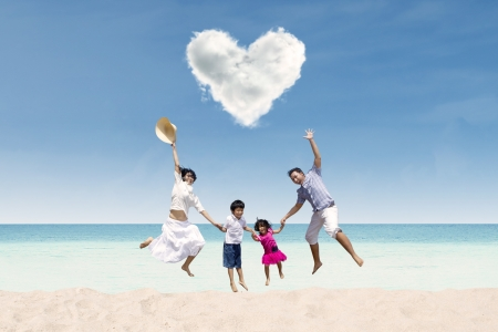 whitehaven beach: Happy Asian family jumping under love cloud at beach Stock Photo