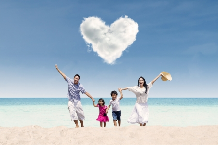 Happy Asian family run at beach under love cloud