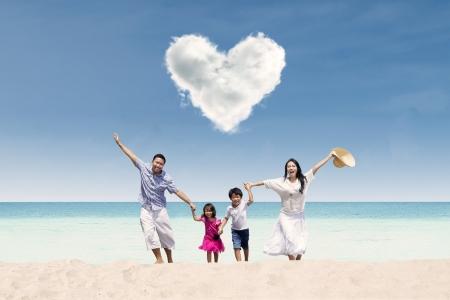 Happy Asian family run at beach under love cloud