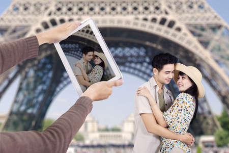 Romantic Asian couple take picture under Eiffel Tower Paris photo