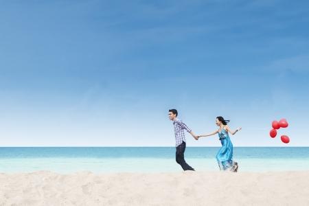 Laufen Paar am Strand wih Luftballons unter blauem Himmel Standard-Bild