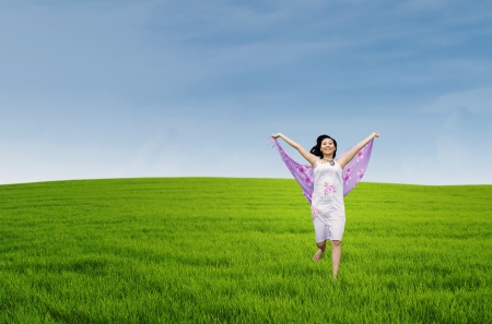 breeze: Young asian woman enjoying freedom by sarong on the meadow Stock Photo
