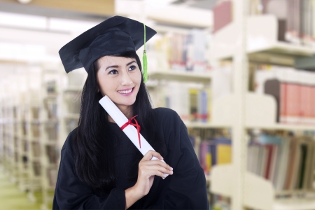 Happy Asian graduate wearing graduation gown at library  photo