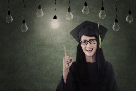 egresado: Graduado femenino feliz bajo las bombillas de la clase