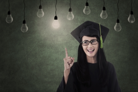 Happy female graduate under light bulbs in class photo