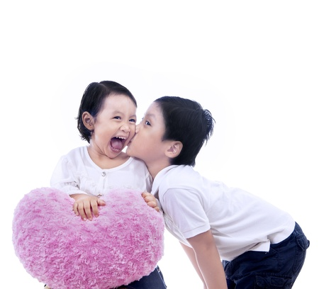 Boy kissing a girl, holding pink heart pillow on white background photo
