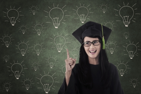 light classroom: Happy student graduate standing in front of light bulbs chalkboard drawing Stock Photo