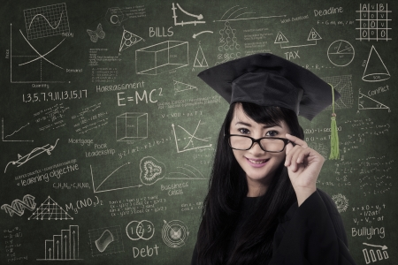 Happy asian woman in graduation gown at class photo